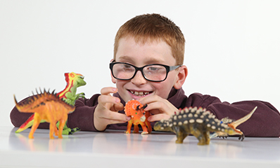 Young boy with glasses playing with toy dinosaurs
