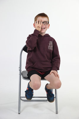 vision impaired boy sitting holding four fingers up