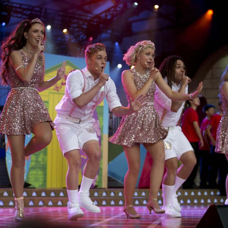 photo of Hi-5 on stage during a performance. The female singers are wearing gold shiny dresses and the male singers are weaing white shorts, white shirts and, white shoes and socks.