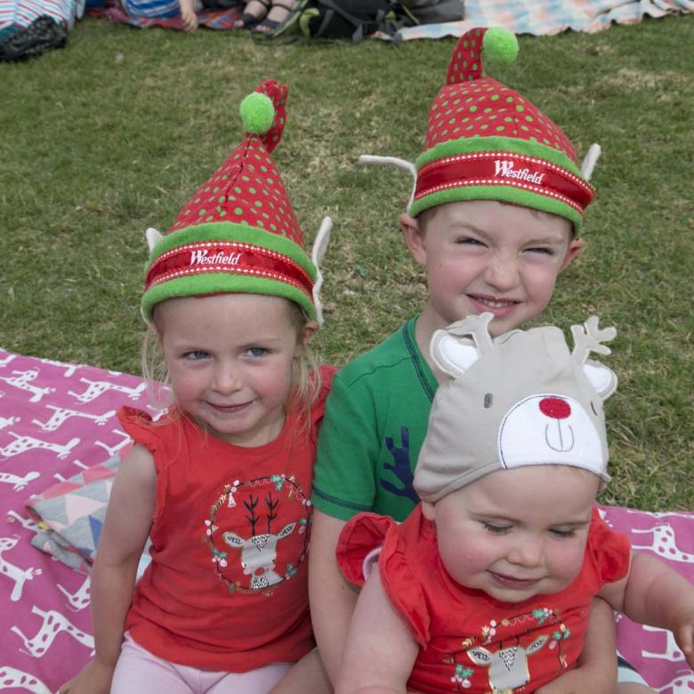photo of three young children Carols guests smiling and wearing Christmas T-shirts and decorative Christmas hats.