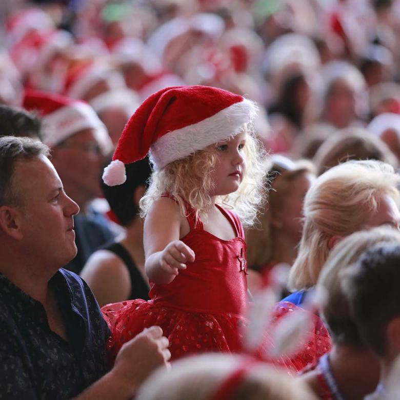 photo of the Carols crowd focusing on a father and daughter watching performances. The daugter is wearing a red outfit and a santa hat