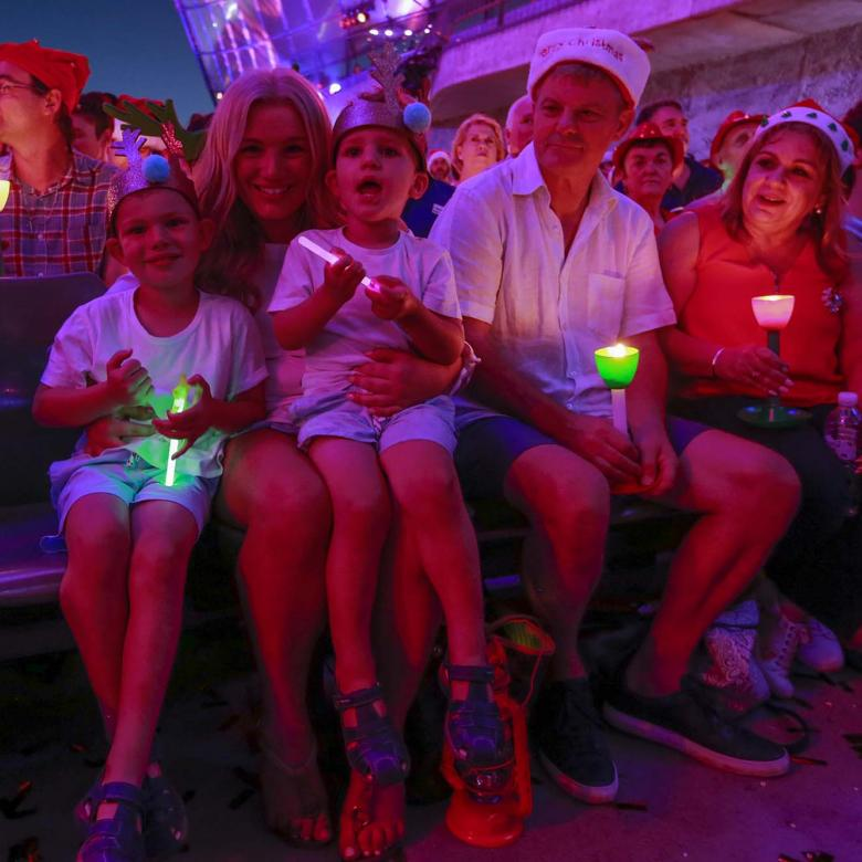 photo of a family sitting in the audience holding their glowing candles and looking happy