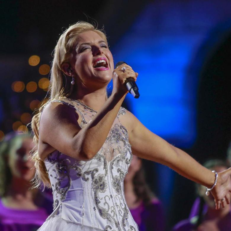 photo of Lucy Durack wearing a white dress and singing with the Australian Girls' Choir singers wearing purple tunics