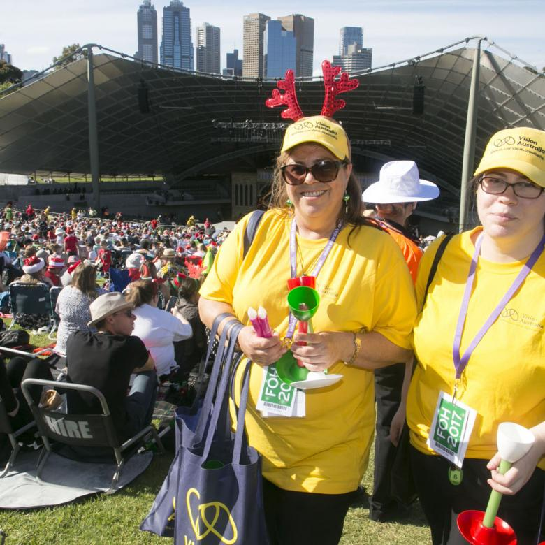 photo of two Carols volunteer event staff wearing yellow t-shirts standing with the crowd and stage behind them