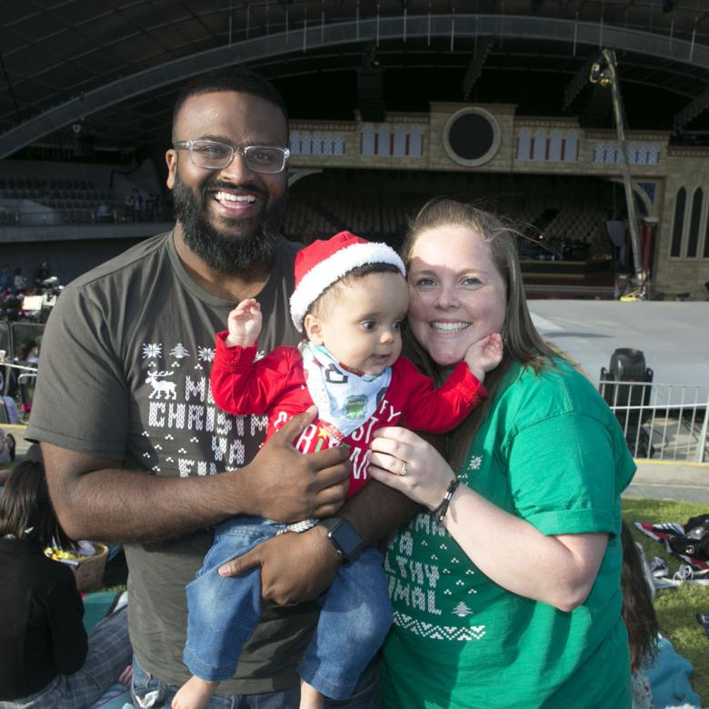 photo of man, woman and baby standing in front of the Carols stage looking happy