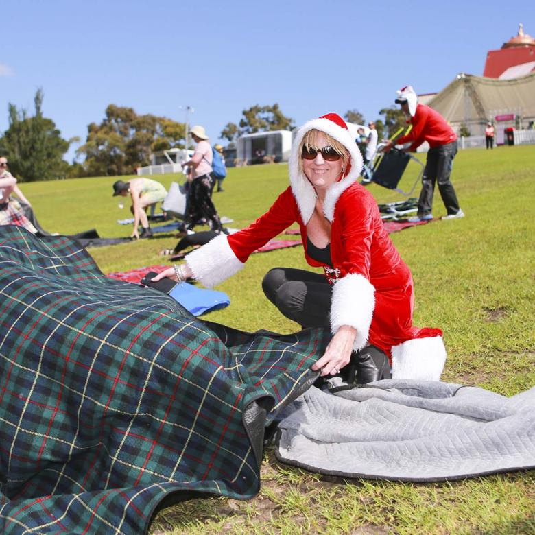 photo of a Carols guest wearing red sitting on a picnic blanket on the grass looking happy