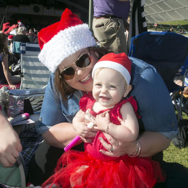 photo of a woman wearing a santa hat and a baby wearing a red dress and a santa hat in her arms. Both look happy and are sitting on the grass
