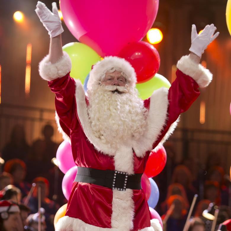 Photo of Santa on the Carols stage with his arms in the air during a performance