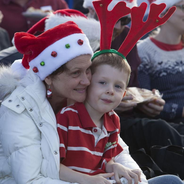 photo of a young boy sitting on the lap of a woman. He is wearing a headband with antlers on and she is wearing a santa hat