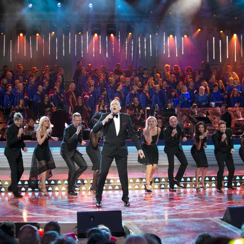 Photo of the Carols stage during a performance by Darren Percival wearing a black suit and the Melbourne Gospel Choir wearing black suits and dresses