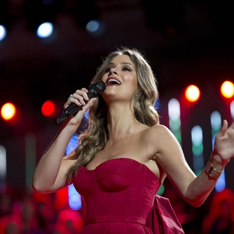 A close-up photo of a Carols by Candlelight performance by Chirstie Whelan-Brown wearing a red dress and singing into a handheld microphone