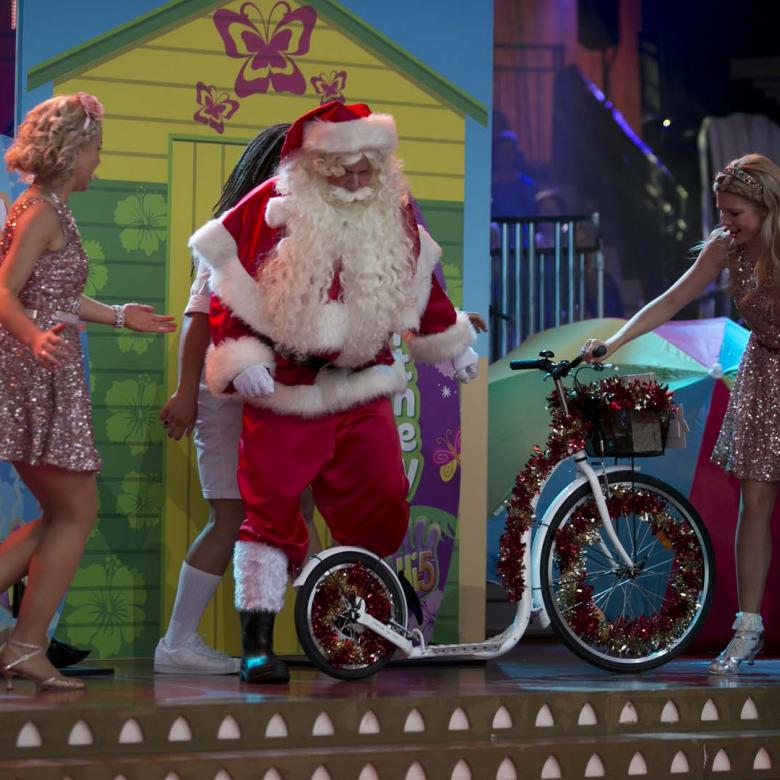 Photo of Santa with the members of Hi-5 standing around a bicycle