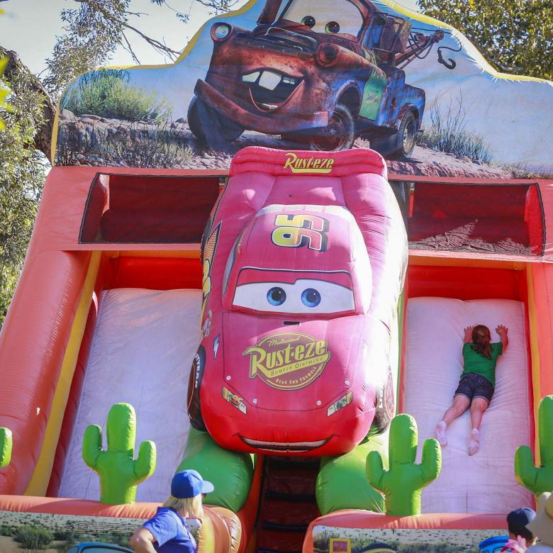 Photo of an inflatable slide for children with an animated character on it. There is a child sliding down.