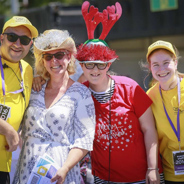 Photo of volunteer event staff wearing yellow branded T-shirt and carols guests looking happy