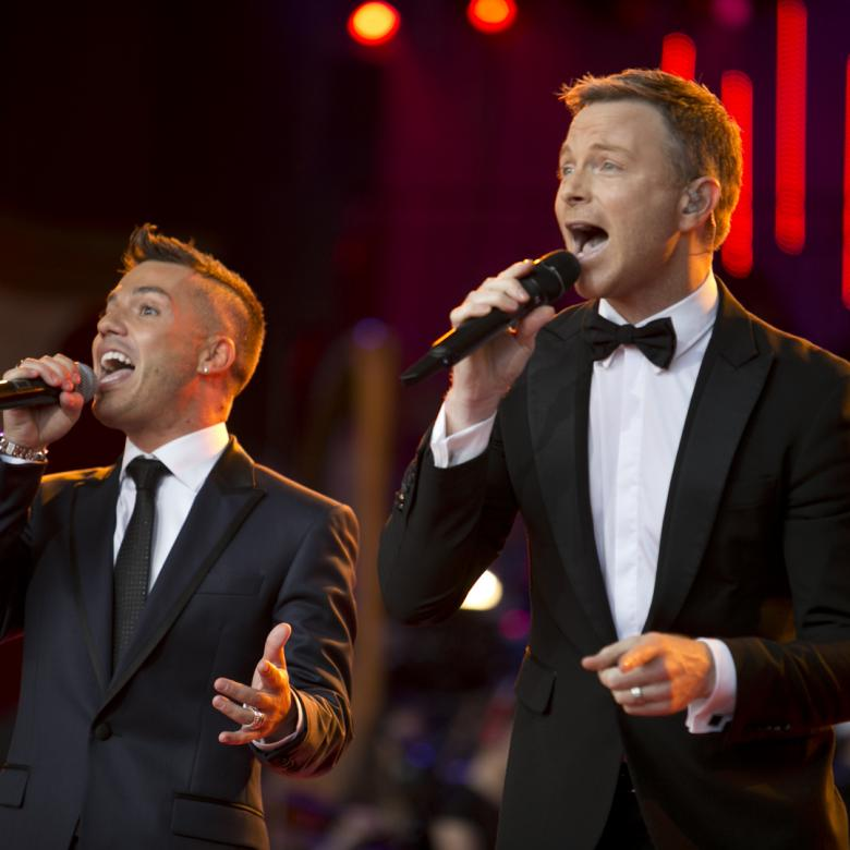 Photo of Anthony Callea and Tim Campbell singing together. Anthony Callea is wearing a black tie and Tim Campbell is wearing a black bowtie and both are wearing suits and singing into handheld microphones