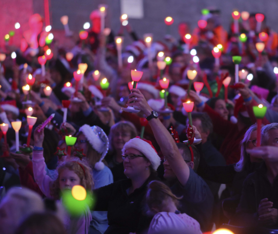 A large group of people sitting in the seated stalls section at Carols by Candlelight.  They are holding green and red candles and pink glowsticks up in the air, while they look towards the stage. A number of people are wearing Santa hats and Christmas accessories.