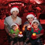 Family of four sitting outside carols by candlelight performance